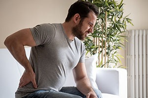 man-with-back-pain-from-injury-at-home-sitting-on-couch